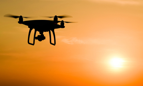 Silhouette of a drone against sunset background